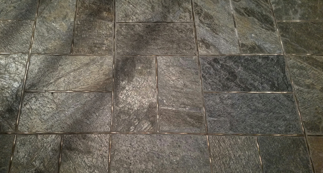 Metal accent tiles and liners: Flowing Liner inTraditional Bronze set in a slate floor