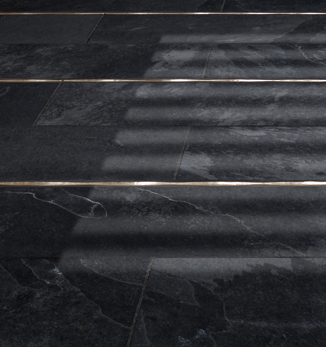 Metal accent liners: Flowing Liner in Traditonal Bronze in a dark stone floor