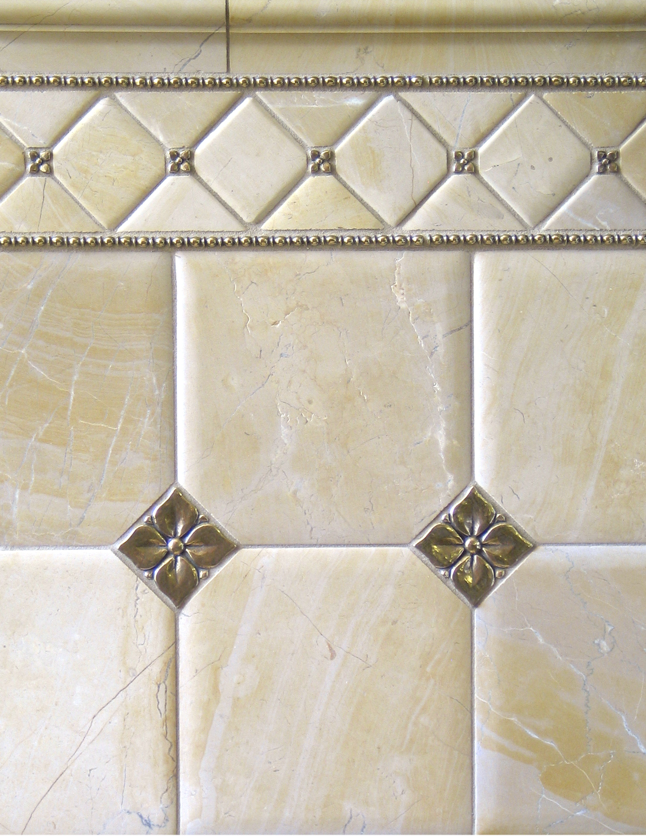 Metal accent tiles and liners: Blooming Leaf and Roman Liner in Traditional Bronze with pillowed limestone