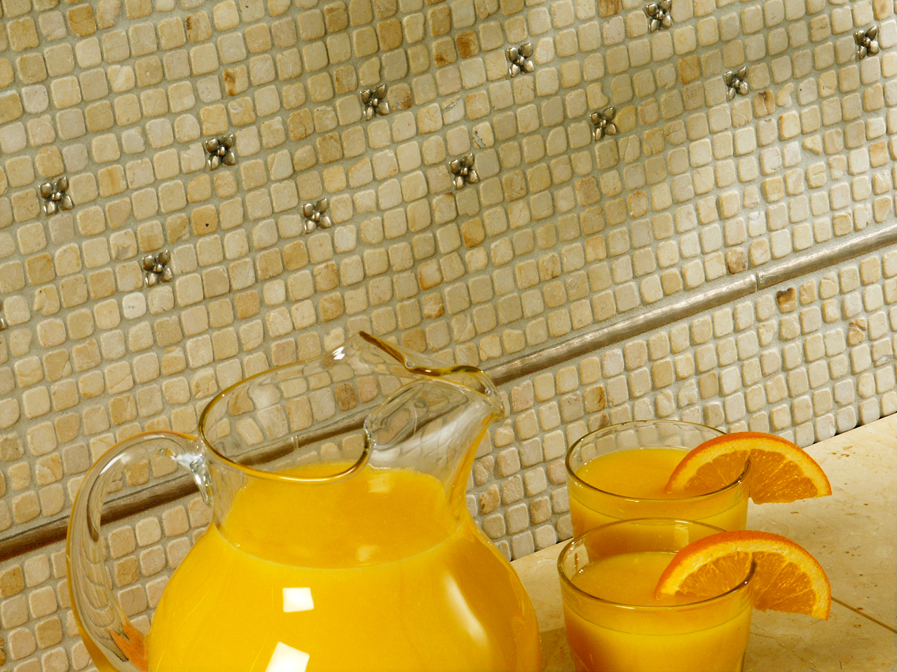 Metal accent tiles and liners: Blooming Leaf and Basic Liner in Traditional Bronze with limestone mosaic