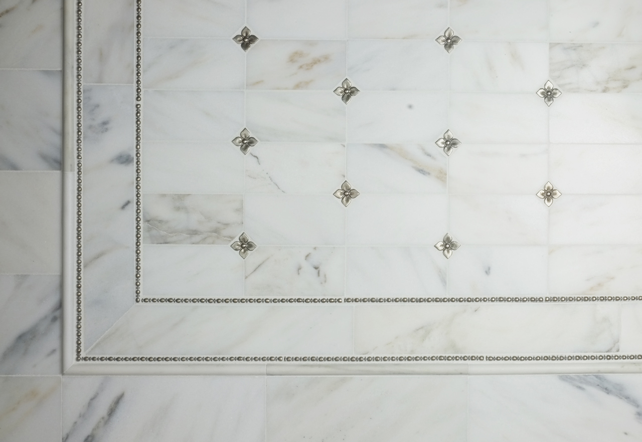 Metal accent tiles and liners: Roman Liner and two sizes of Blooming Leaf in White Bronze with marble