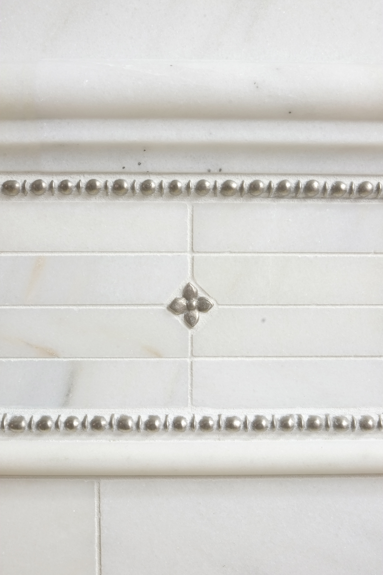 Metal accent tiles and liners: Roman Liner and Blooming Leaf in White Bronze with marble